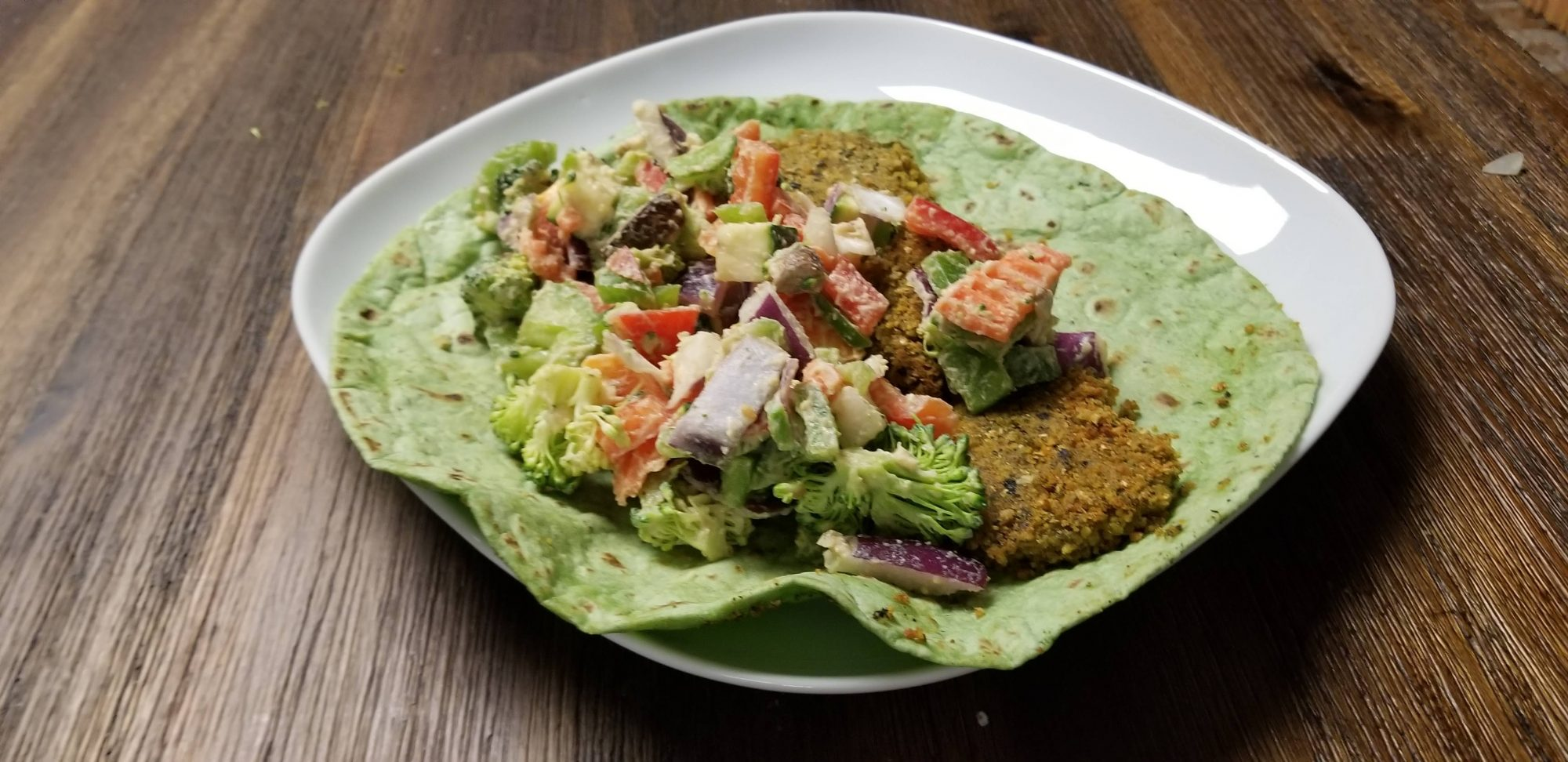 vegan falafel wrap with diced vegetables and hummus